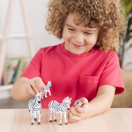 young boy playing with toy zebras.