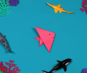 pink paper fish on blue background.