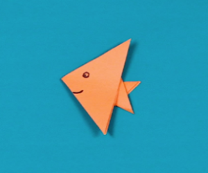 orange paper fish on blue background.