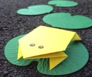 yellow paper frog on green lily pad.