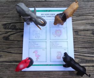 toy flamingo, elephant, lion, and monkey on desk with sheet of paper.