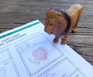 toy lion on desk with sheet of paper.