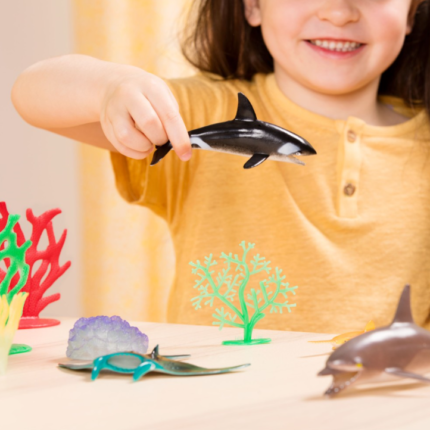 young girl playing with toy whale.